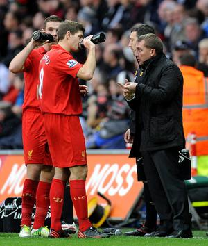 Liverpool manager Brendan Rodgers (right) speaks with Steven Gerrard on the touchline during the Barclays Premier League match at the Liberty Stadium, Swansea
