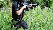 An armed policeman is seen around the village of Rothbury, Northumberland, as the manhunt for fugitive gunman Raoul Moat continues.