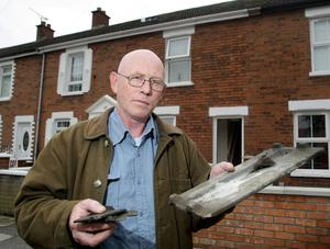 Don Melrose with one of the tiles that fell off his roof in Parkgate Drive, Belfast