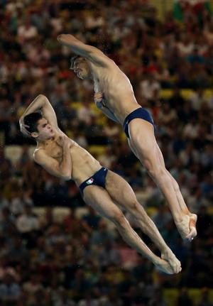 German Sanchez Sanchez and Ivan Garcia Navarro (L) of Mexico look on from the pool deck during the Men's Synchronised 10m Platform Diving on Day 3 of the London 2012 Olympic Games