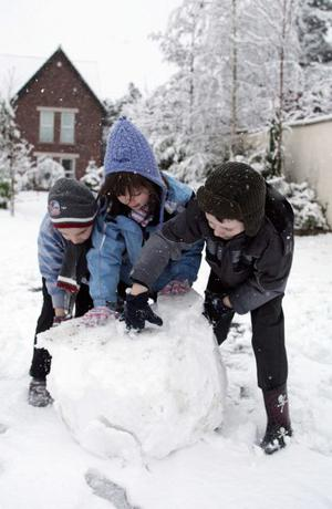 Snow brings Northern Ireland to a stand still.  Left to right. Ciaran McMullan(6), Fiona Lenghan and Matthew O'Rourke from Carryduff pictured outside their houses playing in the snow. February 2009