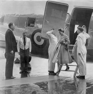 The Queen, Elizabeth 11. 1954 visit.Smiling, the Queen is just about to step on to Ulster soil from the R.A.F. Viking in which she made the flight from Scotland. Lord Wakehurst waits to welcome her.  17/8/1954