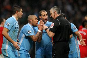 Referee Chris Foy is surrounded by Manchester City players