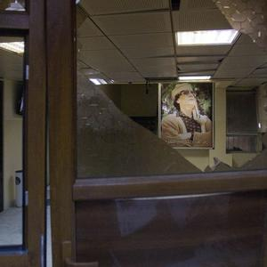 A poster of Muammar Gaddafi is seen in a damaged government building in Tripoli, Libya (AP)