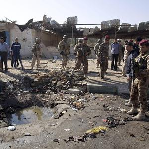 Iraqi security forces inspect the scene of a car bomb attack in Karbala (AP)