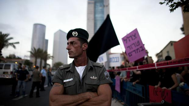 A border policeman looks on as Israeli left-wing protesters demonstrate against Israel's deadly raid on an aid flotilla bound for the blockaded Gaza Strip on May 31, 2010 in Tel Aviv, Israel