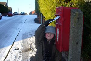 Grandson Caleb Patterson braving the slippery conditions to post some letters. By William McVeigh, Comber