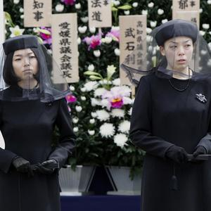 Daughters of the late Prince Tomohito, Akiko, left, and Yoko, attend a funeral for their father in Tokyo (AP)