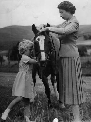 File photo dated 14/09/1955 of Princess Anne helping her mother, Queen Elizabeth II, fit the bridle to the pony 'Greensleeves', the the grounds of Balmoral Castle during the Royal family's summer holiday in Scotland. PRESS ASSOCIATION Photo.