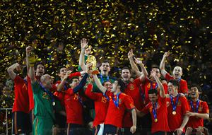 Iker Casillas, captain of Spain (C), and the Spain team celebrate victory with the World Cup trophy  during the 2010 FIFA World Cup South Africa Final match between Netherlands and Spain at Soccer City Stadium on July 11, 2010 in Johannesburg, South Africa