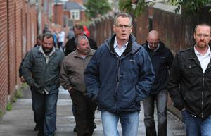 Sinn Féin MLA Gerry Kelly arrives at a rally in Ardoyne to highlight opposition to those who have been  rioting in the area in recent nights July 2010