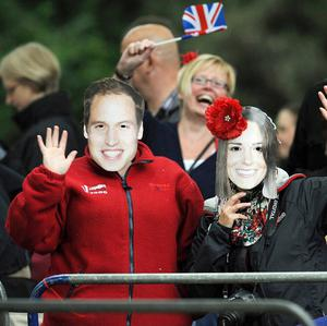 Royal supporters wave along the processional route