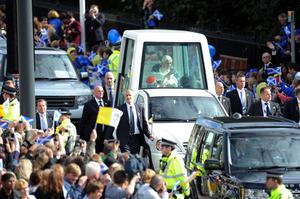 Pope Benedict XVI rides in the Popemobile down Edinburgh's Princes Street on the first day of his four day visit to the United Kingdom