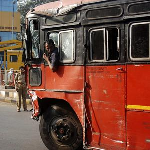 A man drives the damaged bus away after it was driven into numerous vehicles and pedestrians (AP)