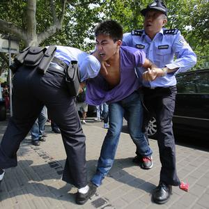 An anti-Japan protester scuffles with police as he tries to march through the streets towards the Japanese Consulate General in Shanghai (AP)