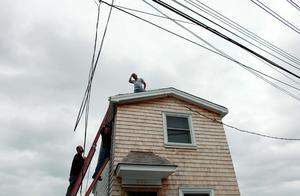 NEW YORK, NY - OCTOBER 28:  People secure the power line to a home as Hurricane Sandy approaches on October 28, 2012 in the Rockaway Beach neighborhood of the Queens borough of New York City. New York City Mayor Michael Bloomberg announced a mandatory evacuation on low-lying coastal areas of the city.  Sandy, which has already claimed over 50 lives in the Caribbean is predicted to bring heavy winds and floodwaters to the mid-Atlantic region. (Photo by Allison Joyce/Getty Images)