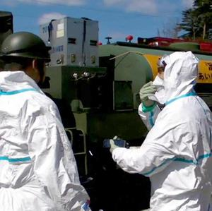Japan Self-Defence Forces personnel prepare to spray water on Unit 3 of the troubled Fukushima Dai-ichi nuclear complex (AP)