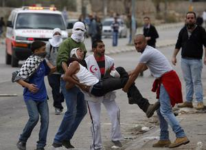 Palestinian carry an injured youth during a protest against Israel's operations in Gaza Strip, outside Ofer, an Israeli military prison near the West Bank city of Ramallah, Sunday, Nov. 18, 2012. (AP Photo/Majdi Mohammed)