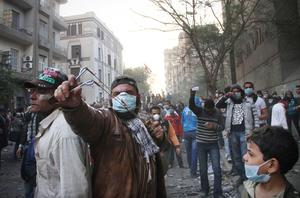 An Egyptian protester uses a handmade sling shot to throw rocks toward Egyptian riot police in Cairo, Egypt, Monday, Nov. 21, 2011. Security forces fired tear gas and clashed Monday with several thousand protesters in Cairo's Tahrir Square in the third straight day of violence that has killed dozens of people and has turned into the most sustained challenge yet to the rule of Egypt's military. (AP Photo)