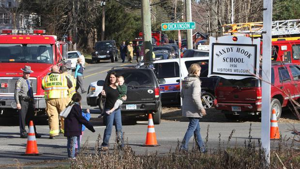 Parents walk away from the Sandy Hook  Elementary School with their children following a shooting, Friday, Dec. 14, 2012 in Newtown, Conn. A man opened fire inside the Connecticut elementary school where his mother worked Friday, killing 26 people, including 18 children, and forcing students to cower in classrooms and then flee with the help of teachers and police. (AP Photo/The Journal News, Frank Becerra Jr.) MANDATORY CREDIT, NYC OUT, NO SALES, TV OUT, NEWSDAY OUT; MAGS OUT