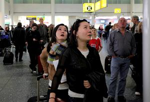 People wait for information in the departure lounge at Gatwick airport
