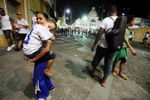 SALVADOR, BRAZIL - FEBRUARY 16: A girl carries a boy on the first day of Carnival celebrations on February 16, 2012 in Salvador, Brazil. Carnival is the grandest holiday in Brazil, annually drawing millions in raucous celebrations culminating on Fat Tuesday before the start of the Catholic season of Lent which begins on Ash Wednesday. Salvador is the capital of the Northeastern state of Bahia and was the first colonial capital of Brazil. Police strikes in Salvador and Rio de Janiero in recent weeks threatened Carnival and raised questions about the countryÄôs preparedness to host the upcoming 2014 World Cup and 2016 Summer Olympics. Rio de JanieroÄôs Carnival begins tomorrow. (Photo by Mario Tama/Getty Images)