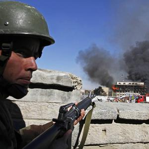 Afghan policeman is on guard as a building burns in central Kabul, Afghanistan (AP)