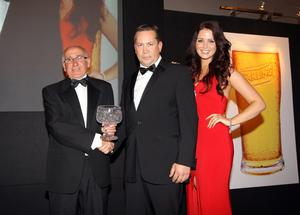 Don Horner from Ballyclare Comrades was awarded the Carling Merit award. Pictured presenting the award to Eric is NIFWA Chairman Stephen Looney pictured with Carling girl Mellissa Patton