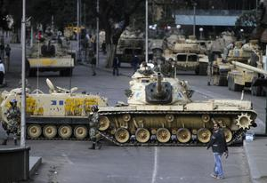 A man walks past military vehicles blocking a street in Cairo, Sunday, Jan. 30, 2011. The Arab world's most populous nation appeared to be swiftly moving closer to a point at which it either dissolves into widespread chaos or the military expands its presence and control of the streets. (AP Photo/Ahmed Ali)