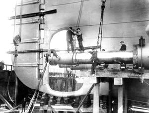 Shipyard men fitting the starboard tailshaft of the Titanic prior to her launch. Photograph © National Museums Northern Ireland. Collection Harland & Wolff, Ulster Folk & Transport Museum