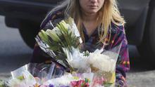 A mourner places flowers at a makeshift memorial at a sign for the Sandy Hook school (AP)