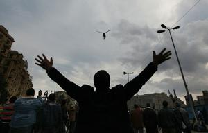 CAIRO, EGYPT - JANUARY 30:  People in Tahrir Square gesture at a low flying police helicopter as the curfew begins on January 30, 2011 in Cairo, Egypt. Cairo remained in a state of flux and marchers continued to protest in the streets and defy curfew, demanding the resignation of Egyptian president Hosni Mubarek. As President Mubarak struggles to regain control after five days of protests he has appointed Omar Suleiman as vice-president. The present death toll stands at 100 and up to 2,000 people are thought to have been injured during the clashes which started last Tuesday. Overnight it was reported that thousands of inmates from the Wadi Naturn prison had escaped and that Egyptians were forming vigilante groups in order to protect their homes.   (Photo by Peter Macdiarmid/Getty Images) *** BESTPIX ***