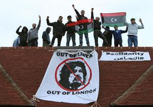 """Members of a group calling themselves """"Topple The Tyrants"""" shout from the rooftop after taking over a house thought to belong to Saif al-Islam Gaddafi, the second son of the Libyan dictator, in Hampstead Garden Suburb, north London . PRESS ASSOCIATION Photo. Picture date: Wednesday March 9, 2011. Photo credit should read: Dominic Lipinski/PA Wire"""