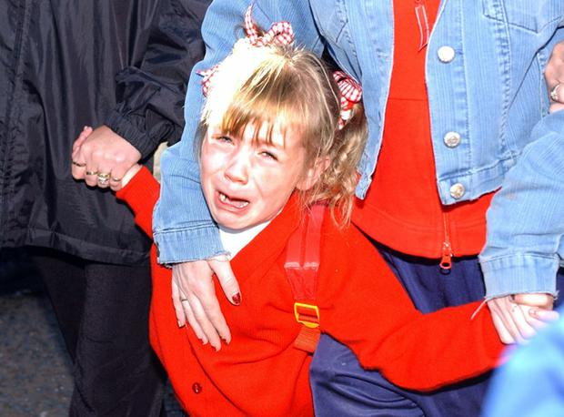 Alice Lee Bunting in tears as she makes her way to Holy Cross Primary School