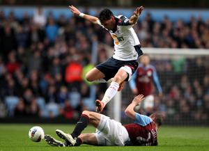 BIRMINGHAM, ENGLAND - APRIL 24:  Chris Eagles of Bolton Wanderers hurdles the challenge of Carlos Cuellar of Aston Villa during the Barclays Premier League match between Aston Villa and Bolton Wanderers at Villa Park on April 24, 2012 in Birmingham, England. (Photo by Michael Steele/Getty Images)
