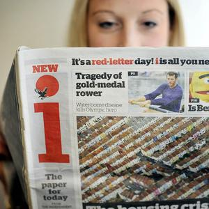 A person reads Britain's first new daily national newspaper in nearly 25 years, the tabloid-format 'i'