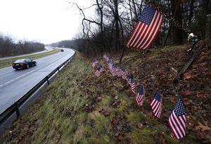 Twenty-seven small U.S. flags adorn a large flag on a makeshift memorial on the side of Highway 84 near the Newtown, Conn., town line as residents mourn victims killed by gunman Adam Lanza, Monday, Dec. 17, 2012. Authorities say Lanza killed his mother at their home and then opened fire inside the Sandy Hook Elementary School in Newtown, killing 26 people, including 20 children, before taking his own life, on Friday. (AP Photo/Julio Cortez)
