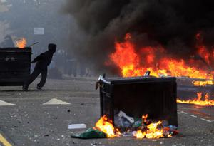 A masked youth pulls a burning garbage bin set on fire by rioters in Hackney, east London, Monday, Aug. 8, 2011