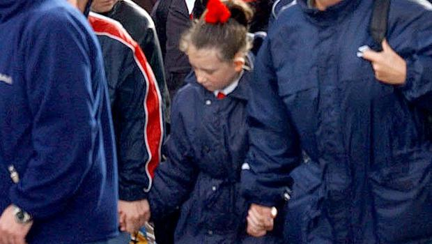 """Paulette Donnelly with her parents arriving at Holy Cross Girls primary School after walking through """"Corridor of Hate"""" on Friday (7/9/01)."""