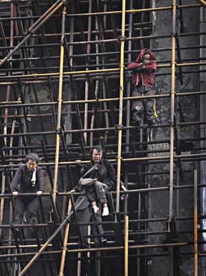 In this Monday, Nov. 15, 2010 photo, residents stand on scaffolding as they wait for help after a fire broke out at the apartment building in the downtown area of Shanghai, east China. Investigators searched Tuesday for the cause of a fire that engulfed a high-rise apartment building under renovation in China's business center of Shanghai, killing 49 people and sending residents scrambling down scaffolding to escape. (AP Photo) ** CHINA OUT **