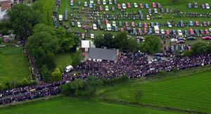 Thousands of mourners follow the coffin of racing legent Joey Dunlop at his funeral in Ballymoney. July 2000.