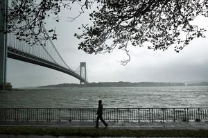 NEW YORK, NY - OCTOBER 29:  A man walks near the Verrazano Bridge as Hurricane Sandy begins to affect the area on October 29, 2012 in the in Brooklyn borough of New York City.  The storm, which threatens 50 million people in the eastern third of the U.S., is expected to bring days of rain, high winds and possibly heavy snow. New York Governor Andrew Cuomo announced the closure of all New York City bus, subway and commuter rail service as of Sunday evening.  (Photo by Spencer Platt/Getty Images) *** BESTPIX ***