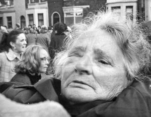 A woman, her face swollen atfer a confrontation with Paratroopers outside Tennant Street RUC Station is carrieed away. Members of the Loyalist Women's Action Committee had been holding a protest.  8/9/1972