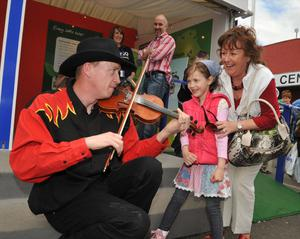 Performing on the Tesco stand at the Balmoral Show, fiddler Adam with Emma McBride from Ballycastle age 5 and Joan Cary from Belfas