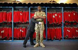 WINDSOR, ENGLAND - APRIL 21:  Irish Guardsman Bortnill St'Ange is measured for his ceremonial uniform by Master Tailor Lance Sergeant Matthew Else in the store room at Victoria Barracks on April 21, 2011 in Windsor, England. The Irish Guards returned from active duty in Afghanistan at the beginning of April, and are now preparing for ceremonial duties. Prince William is the Colonel of the Regiment and the Irish Guards will be on duty at the Royal Wedding on April 29, 2011.  (Photo by Peter Macdiarmid/Getty Images) *** Local Caption *** Bortnill St'Ange;