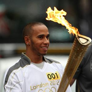 Formula One driver Lewis Hamilton holding the Olympic Flame before his Torch Relay leg through Luton (Locog/PA)