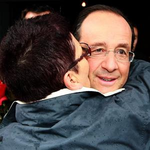 A woman kisses French president Francois Hollande as he leaves the polling station after voting in the French parliamentary elections in Tulle (AP)