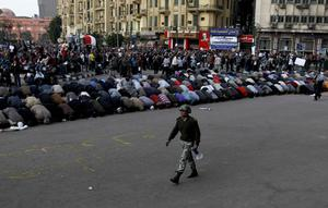 An Egyptian soldier walks past anti-government protesters as they pray in Tahrir Square in Cairo, Egypt, Sunday, Jan. 30, 2011.  (AP Photo/Tara Todras-Whitehill)