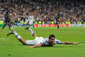 MADRID, SPAIN - APRIL 05:  Angel Di Maria (R) of Real Madrid slides on the pitch as he celebrates scoring during the UEFA Champions League quarter final first leg match between Real Madrid and Tottenham Hotspur at Estadio Santiago Bernabeu on April 5, 2011 in Madrid, Spain.  (Photo by Jasper Juinen/Getty Images)