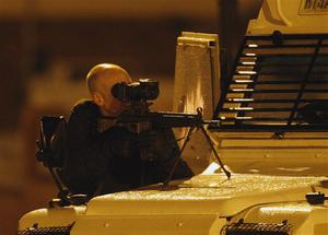 A Police Service of Northern Ireland officer aims his rifle as he takes up position near Lismore Manor, Craigavon, Northern Ireland, Tuesday, March 10, 2009. A large security presence has begun after a Police Service of Northern Ireland officer was shot dead by suspected Irish Republican terrorists.  (AP Photo/Peter Morrison)